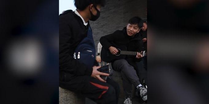 他背吉他在火车站唱歌:为回家的人送温暖